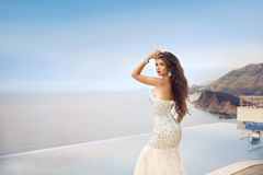 Beautiful fashion bride girl in beaded wedding dress. Summer hol. Iday concept. Luxury resort woman in long gown posing by infinity swim pool over sunset sky royalty free stock photography