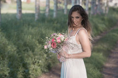 Beautiful fashion bride with a perfect skin and amazing green eyes in a forest. Young fashion bride with perfect skin and green eyes holding a wedding bouquet stock photography
