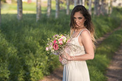 Beautiful fashion bride with a perfect skin and amazing green eyes in a forest. Young fashion bride with perfect skin and green eyes holding a wedding bouquet royalty free stock photography