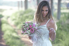 Beautiful fashion bride with a perfect skin and amazing green eyes in a forest. Young fashion bride with perfect skin and green eyes holding a wedding bouquet stock photos