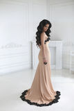 Beautiful fashion brunette woman in elegant dress with long wavy stock photos