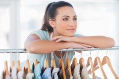 Beautiful fashion designer leaning on clothes Stock Image