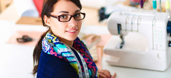 Beautiful fashion designer sitting at the desk in studio stock image
