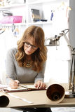 Beautiful fashion designer working in her studio Stock Image