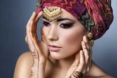 Beautiful fashion east  woman portrait with oriental accessories. Earrings, bracelets and rings. Indian girl with  henna tattoos and beauty jewels. Hindu model Royalty Free Stock Image
