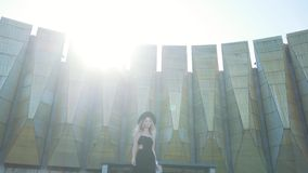 Beautiful fashion girl in black dress posing and smiling at camera on urban architecture background. stock video footage