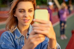 Beautiful fashion girl doing selfie with phone at sunset.  royalty free stock images