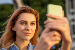 Beautiful fashion girl doing selfie with phone at sunset.  stock image
