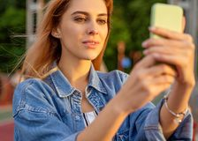Beautiful fashion girl doing selfie with phone at sunset.  royalty free stock photos