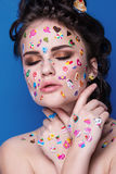 Beautiful fashion girl with luxury professional makeup and funny emoji stickers glued on the face. Young woman with cupcake in hands stock images