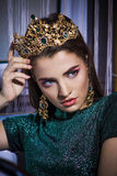 Beautiful fashion girl model with a powerful strict look in the golden crown royalty free stock image
