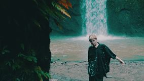 Girl in tropical rain forest jungle. Beautiful fashion girl posing in tropical rain forest jungle near the waterfall. Portrait of stylish hipster female outdoor stock footage