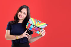 Beautiful fashion girl presenting colorful bag Stock Images