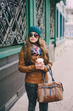 Beautiful fashion girls outdoor. Beautiful model walks through the city in a beautiful hat and glassesr Royalty Free Stock Images