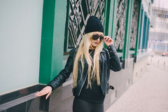 Beautiful fashion girls outdoor. Beautiful model walks through the city in a beautiful hat and glassesr Royalty Free Stock Photos
