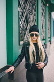 Beautiful fashion girls outdoor. Beautiful model walks through the city in a beautiful hat and glassesr Stock Image