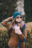 Beautiful fashion girls outdoor. Beautiful model walks through the city in a beautiful hat and glassesr Royalty Free Stock Photo