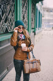 Beautiful fashion girls outdoor. Beautiful model walks through the city in a beautiful hat and glassesr Stock Images
