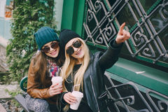 Beautiful fashion girls outdoor. Beautiful models walks through the city in a beautiful hat and glassesr stock photography
