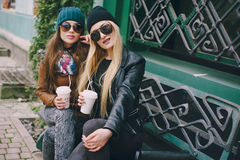 Beautiful fashion girls outdoor. Beautiful models walks through the city in a beautiful hat and glassesr Royalty Free Stock Photos