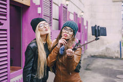 Beautiful fashion girls outdoor. Two beautiful girls are photographed on the street in hats and classy jackets Stock Images