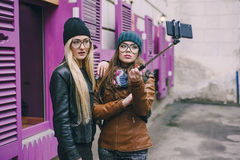 Beautiful fashion girls outdoor. Two beautiful girls are photographed on the street in hats and classy jackets stock photography