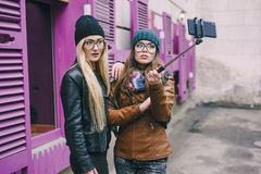 Beautiful fashion girls outdoor. Two beautiful girls are photographed on the street in hats and classy jackets royalty free stock image
