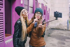 Beautiful fashion girls outdoor. Two beautiful girls are photographed on the street in hats and classy jackets Royalty Free Stock Images