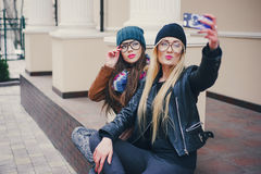 Beautiful fashion girls outdoor. Two beautiful girls are photographed on the street in hats and classy jacketsr Stock Photo