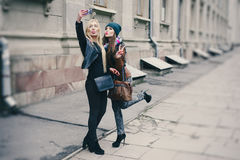 Beautiful fashion girls outdoor. Two beautiful girls are photographed on the street in hats and classy jacketsr Stock Photos