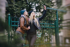 Beautiful fashion girls outdoor. Two beautiful girls are photographed on the street in hats and classy jacketsr Royalty Free Stock Photos