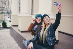Beautiful fashion girls outdoor. Two beautiful girls are photographed on the street in hats and classy jacketsr royalty free stock photography