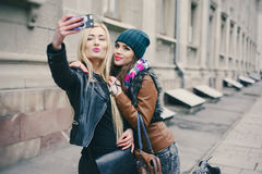 Beautiful fashion girls outdoor. Two beautiful girls are photographed on the street in hats and classy jacketsr Stock Images