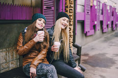 Beautiful fashion girls outdoor. Two beautiful girls walk around town fashionably and stylishly dressed with a Cup of coffee Royalty Free Stock Image