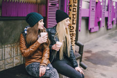 Beautiful fashion girls outdoor. Two beautiful girls walk around town fashionably and stylishly dressed with a Cup of coffee royalty free stock photo