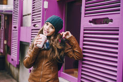 Beautiful fashion girls outdoor. Two beautiful girls walk around town fashionably and stylishly dressed with a Cup of coffee Stock Image