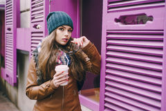 Beautiful fashion girls outdoor. Two beautiful girls walk around town fashionably and stylishly dressed with a Cup of coffee Stock Photos
