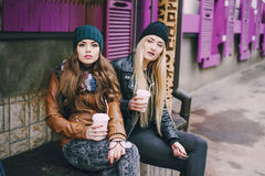 Beautiful fashion girls outdoor. Two beautiful girls walk around town fashionably and stylishly dressed with a Cup of coffee stock photography