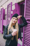 Beautiful fashion girls outdoor. Two beautiful girls walk around town fashionably and stylishly dressed with a Cup of coffee Royalty Free Stock Photography