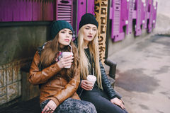 Beautiful fashion girls outdoor. Two beautiful girls walk around town fashionably and stylishly dressed with a Cup of coffee royalty free stock images