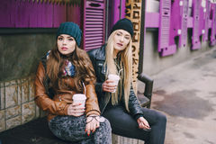 Beautiful fashion girls outdoor. Two beautiful girls walk around town fashionably and stylishly dressed with a Cup of coffee Royalty Free Stock Photos