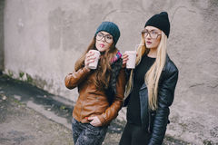 Beautiful fashion girls outdoor. Two beautiful girls walk around town fashionably and stylishly dressed with a Cup of coffeer royalty free stock image