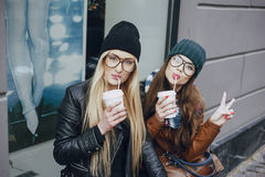 Beautiful fashion girls outdoor. Two beautiful girls walk around town fashionably and stylishly dressed with a Cup of coffeer Stock Photography