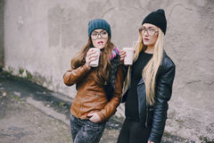 Beautiful fashion girls outdoor. Two beautiful girls walk around town fashionably and stylishly dressed with a Cup of coffeer Stock Photos