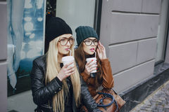 Beautiful fashion girls outdoor. Two beautiful girls walk around town fashionably and stylishly dressed with a Cup of coffeer Royalty Free Stock Photo