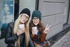 Beautiful fashion girls outdoor. Two beautiful girls walk around town fashionably and stylishly dressed with a Cup of coffeer stock photo