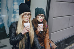 Beautiful fashion girls outdoor. Two beautiful girls walk around town fashionably and stylishly dressed with a Cup of coffeer Royalty Free Stock Images