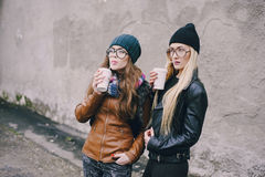 Beautiful fashion girls outdoor. Two beautiful girls walk around town fashionably and stylishly dressed with a Cup of coffeer royalty free stock photography