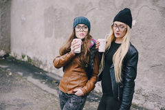 Beautiful fashion girls outdoor. Two beautiful girls walk around town fashionably and stylishly dressed with a Cup of coffeer stock images