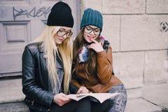 Beautiful fashion girls outdoor. Two beautiful girls walk around town fashionably and stylishly dressedr Stock Photos